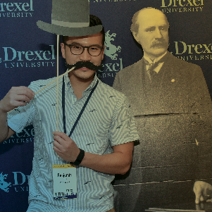 Alumnus posing with mustache and hat prop