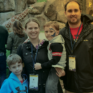 Family posing in front of giraffes at the zoo