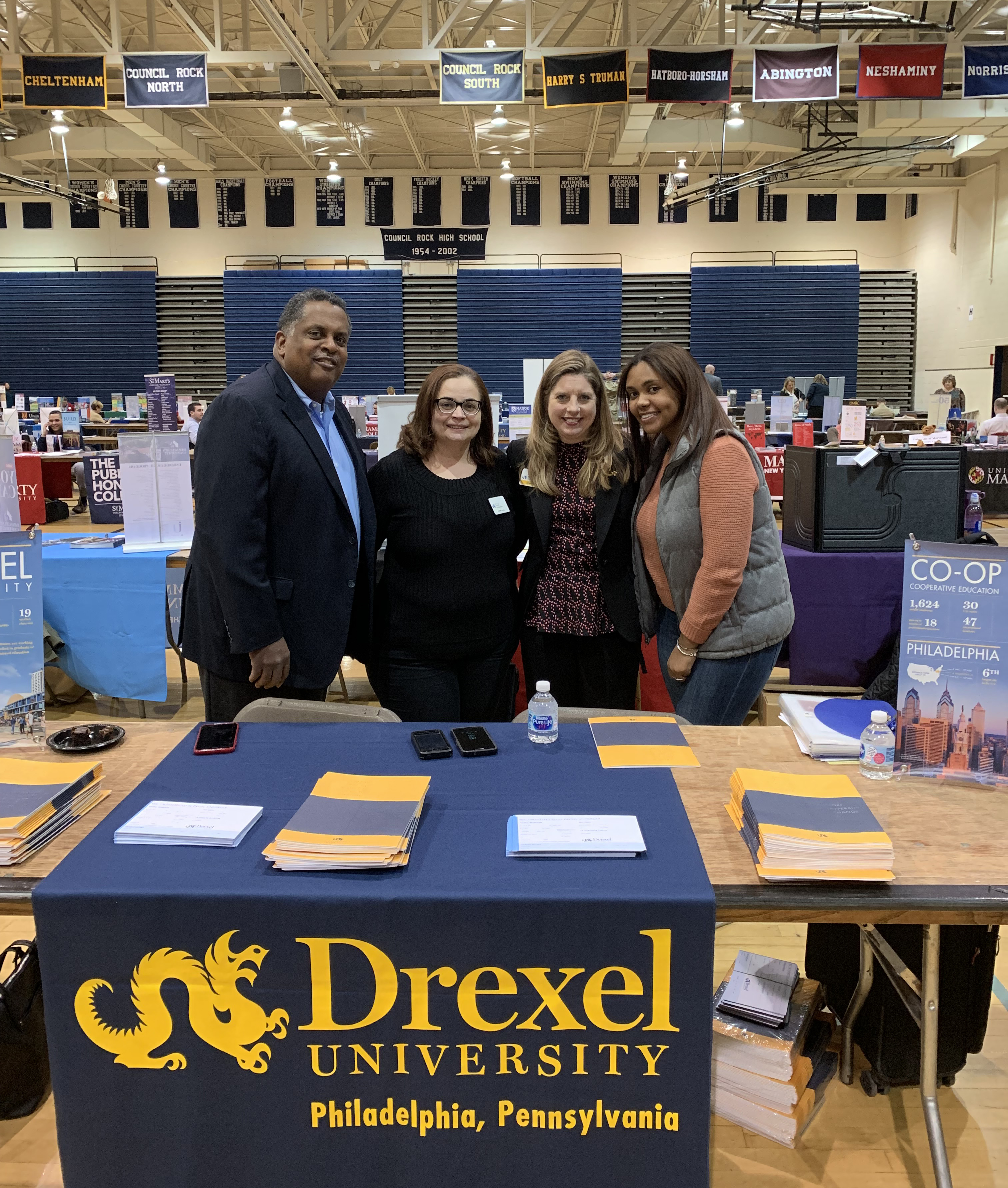 Alumni Ambassadors Carvon Johnson, BS '85, MS '88; Izabelle Gómez, BS '04; Catherine Campbell-Perna, BS '95, MS '11; and Janai Johnson, BS '18 talk to perspective students and their parents at a packed college fair at Council Rock North High School in Bucks County, Pennsylvania.