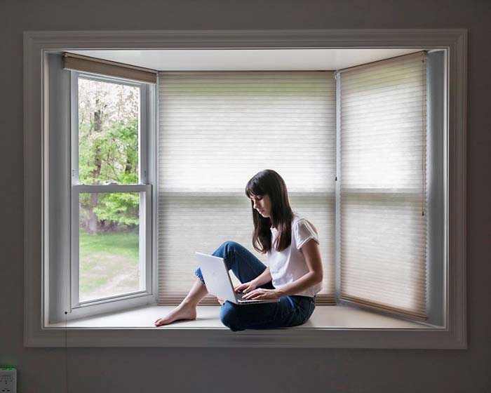girl with laptop in bay window