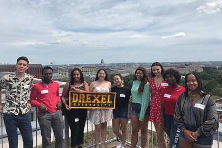 students holding the drexel university sign