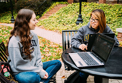 Two students sitting at an outdoor table, working on their laptops