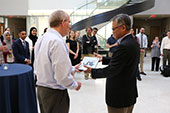 Dean Yi Deng presents Gregory Hislop, PhD, with an award at the May 21 CCI Spring Reception