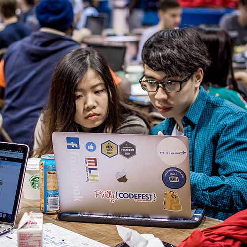 Two students working on a laptop while competing at Philly Codefest