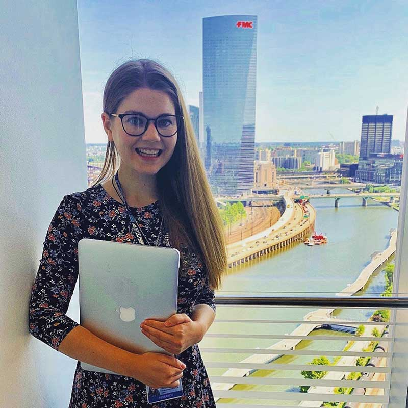 PhD student Elizabeth Campbell photographed in front of a window through which you can see the Philadelphia skyline and FMC building. She is wearing glasses and a floral print dress, holding a laptop and smiling at the camera.