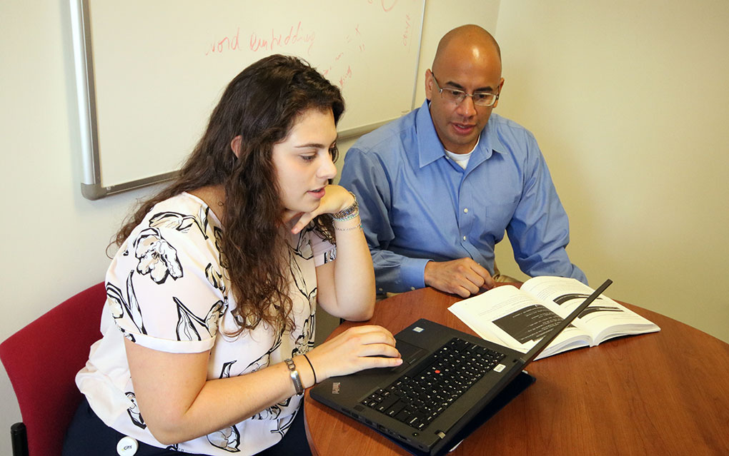 Student and faculty member with computer
