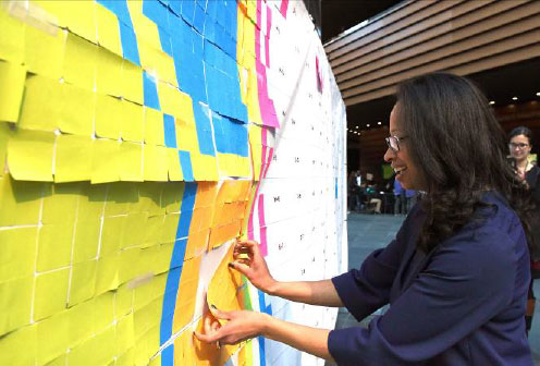 Dalila Wilson-­‐Scott, Senior Vice President for Community Impact at Comcast and President of the Comcast NBCUniversal Foundation adds a Post-­‐it pattern, representing a pixel, to the template that would eventually form a supersized GIF image of the Liberty Bell and Philadelphia Eagles logo by the end of the activity.