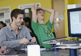 A student throws up his hands in joyful disbelief as another wields the controls of their engineering project.
