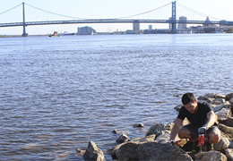 Student cleaning up the Delaware River