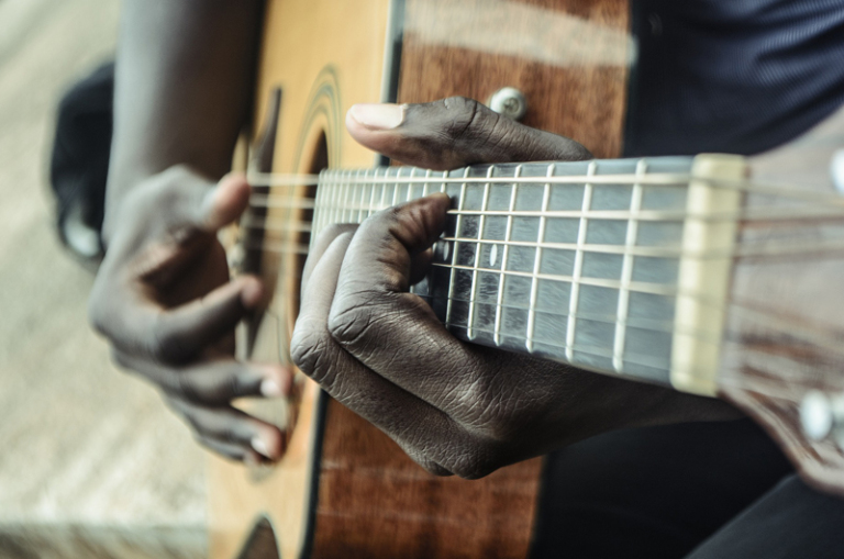Hands strumming a guitar