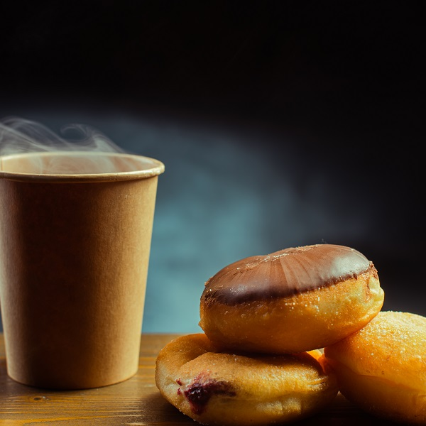 Cup of hot coffee with a stack of donuts