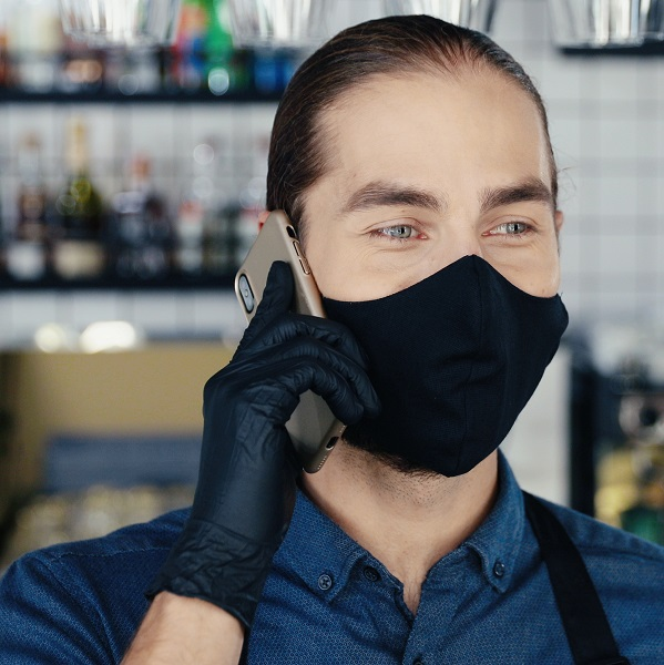 Adult restaurant worker wearing mask taking phone order