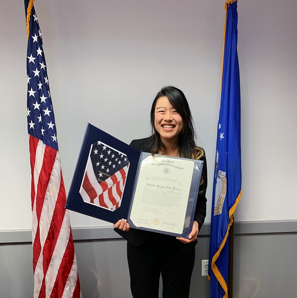 Elizabeth Lee, a physician assistant student, standing next to American flag with notification of Air Force scholarship.
