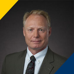 Jeff Ryan Headshot with Drexel Yellow triangle at the top left and Drexel Blue triangle at the bottom right