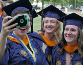 Three women dressed in blue and gold caps and gowns taking a selfie.