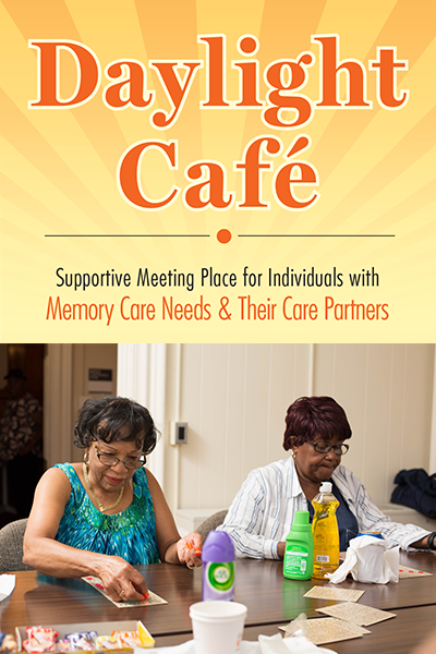 Two older women of color sitting at a table with the Daylight Cafe graphic