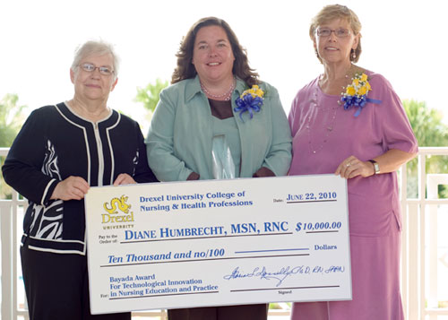 Dean Donnelly presents check with 2 nursing professionals