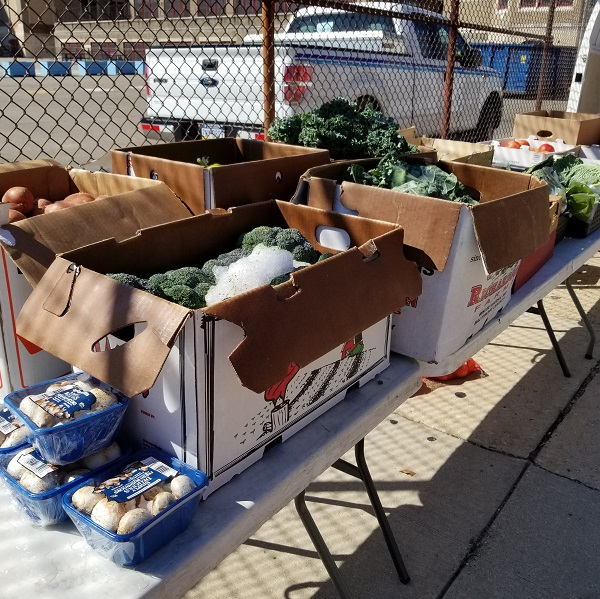 Boxes for fresh vegetables at a farm stand event outside Belmont Charter School