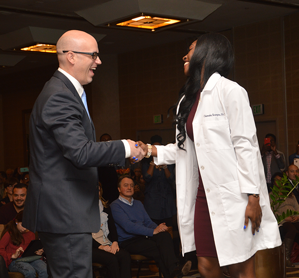 Ryan J. Clancy, MSHS, MA, PA-C, DFAAPA shaking hands with student from PA White Coat Ceremony