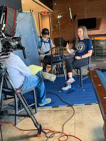 Kellsey Frank in front of a camera wearing a Philadelphia Union shirt