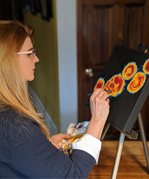 Michele Rattigan painting at a table