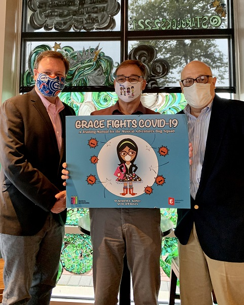 Author Ken Korber holding Grace Fights COVID-19 book cover with Eckhartz Press publishers Rick Kaempfer and David Stern