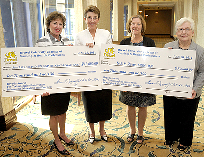 Bayada award winners holding ceremonial checks
