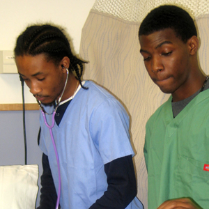 Two high school boys dressed in scrubs participate in hands-on simulation field experience.