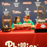 Drexel Students read the triangle while surrounded by Phillies World Series Trophies