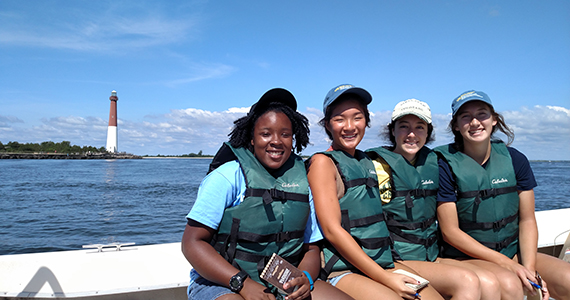 Students on a boat in Barnegat Bay at Drexel's Environmental Science Leadership Academy with the lighthouse