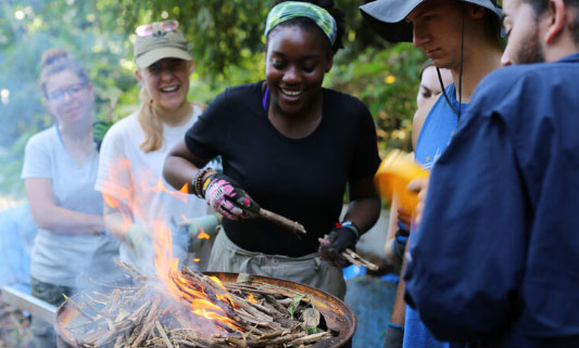 Alexis making biochar with other Drexel students.