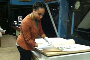 Mica Matlock turns the pages in The Birds of America book at the Academy of Natural Sciences