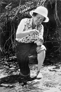 Dr. Ruth Patrick, in her signature pith helmet, collecting organisms from a stream; circa 1970