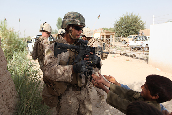 Diaz gives a piece of candy to a local boy while on patrol to discuss quality of life with Afghans in Marjah, Afghanistan.
