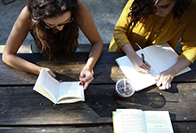 Young women studying at an outdoors table