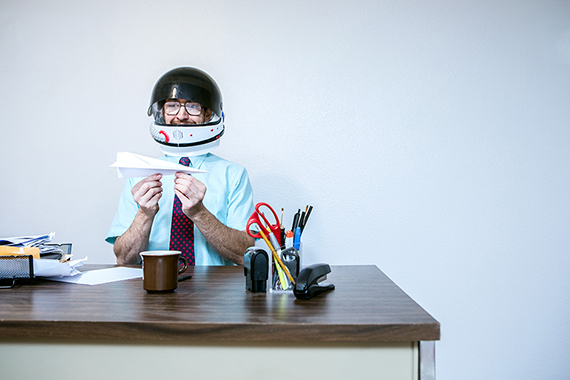 man at a desk wearing a helmet holding a paper airplane