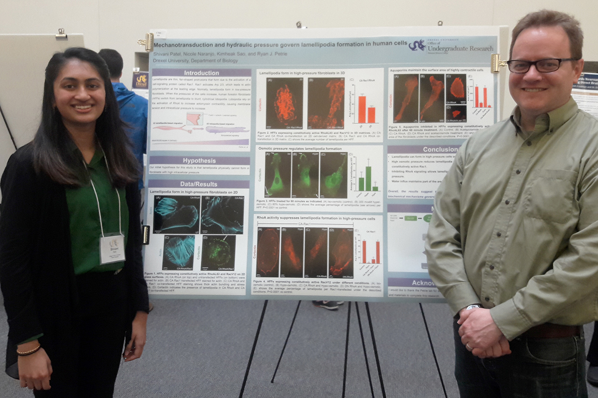 Shivani Patel and Ryan Petrie stand in front of a research poster