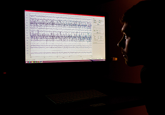 Researcher looking at Brainwaves on Computer Monitor