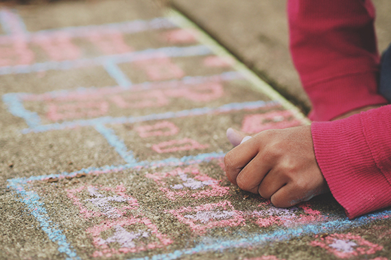 Child drawing with chalk on a sidewalk