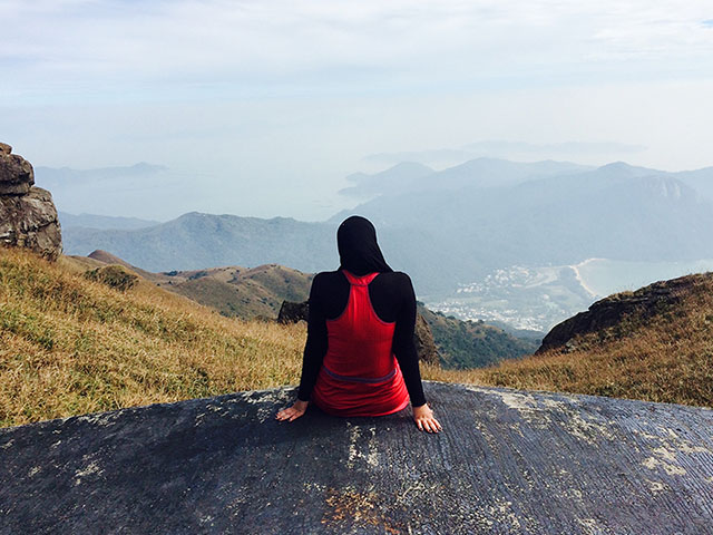 Drexel student sitting on rock in front of view of Chinese landscape