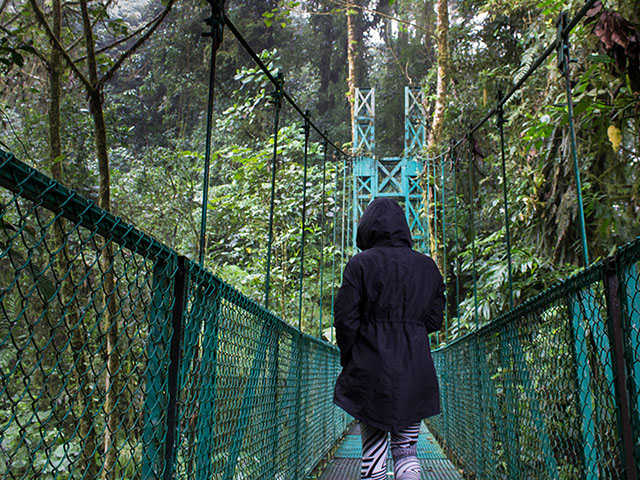 Student crossing a bridge surrounded by forrest of Costa Rica