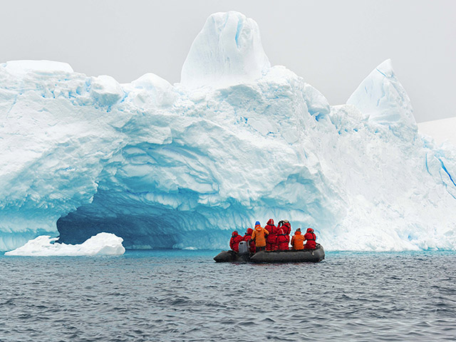 A research team approaches a glacier via boat.