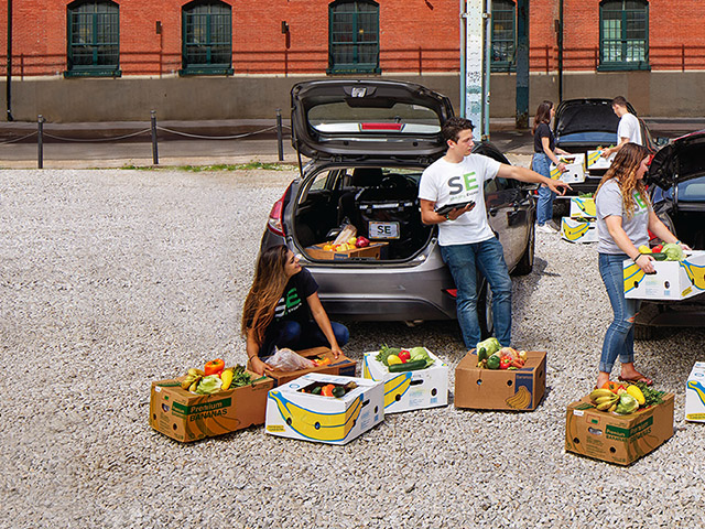 Members of Sharing Excess load food donations into cars