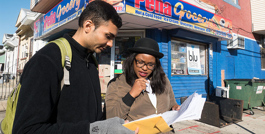 Young man and woman examining their notes, in front of a corner store