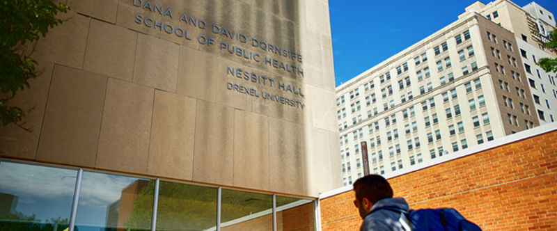 Photo of front of Nesbitt Hall, Dornsife School of Public Health with student about to enter