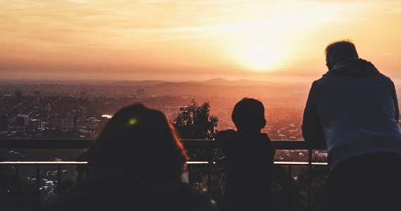 family overlooking city at sunset