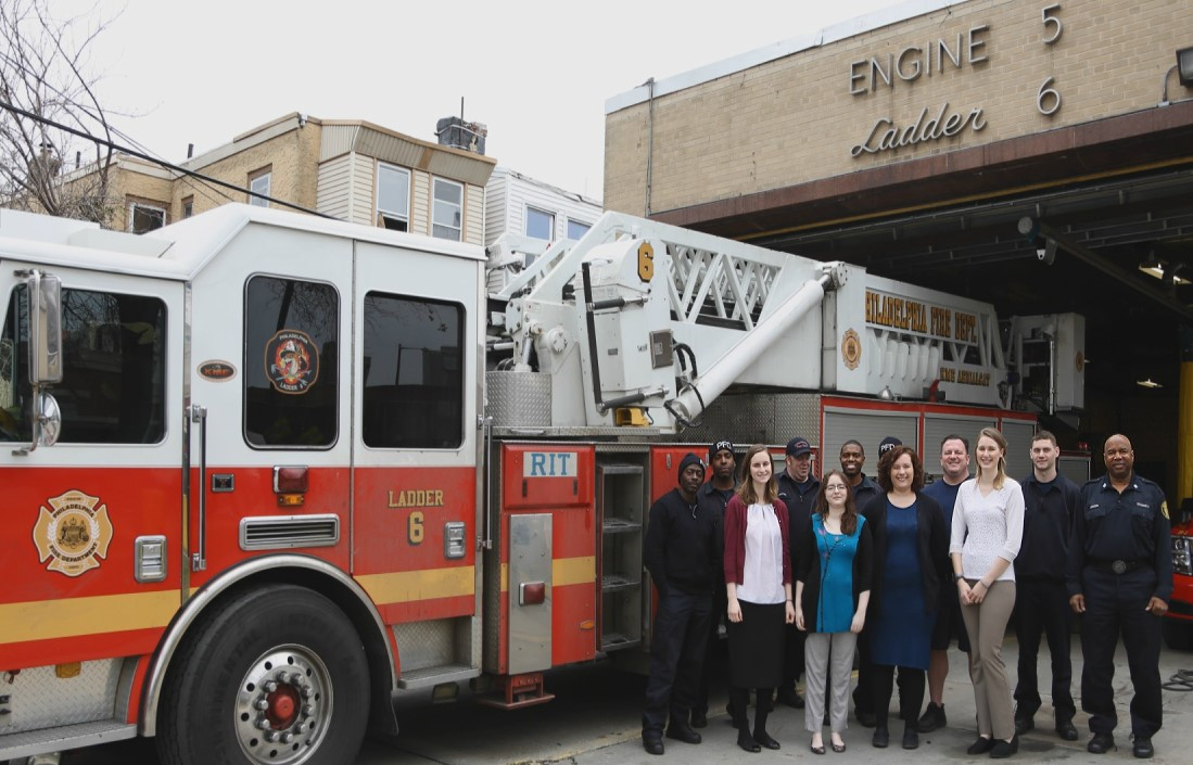 Group of individual standing next to a fire engine