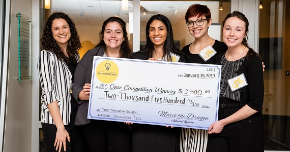 Winning students pose with giant check