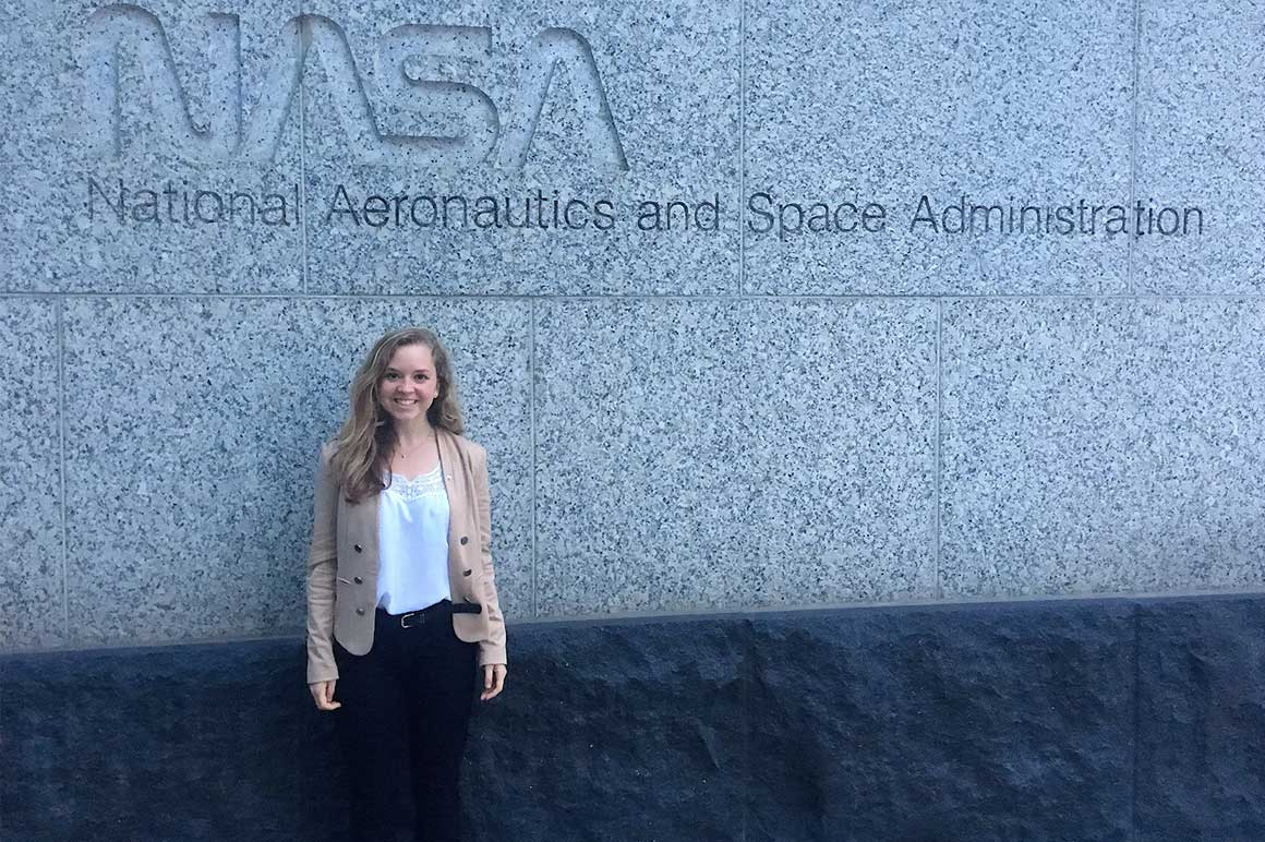 student in front of sign for NASA