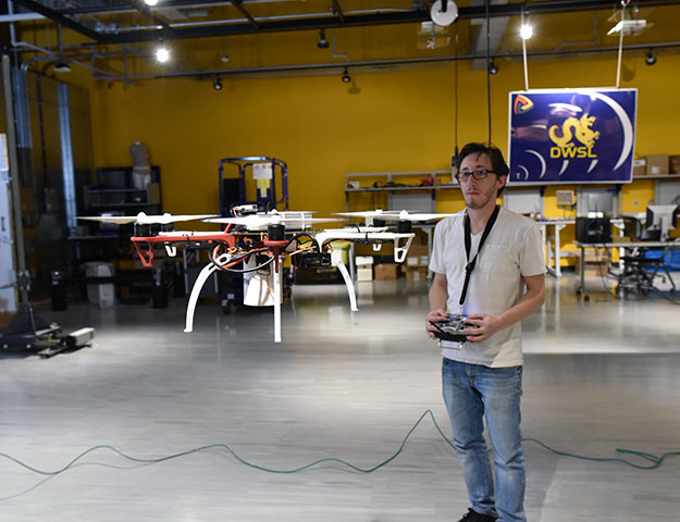 Student working with drone in lab.